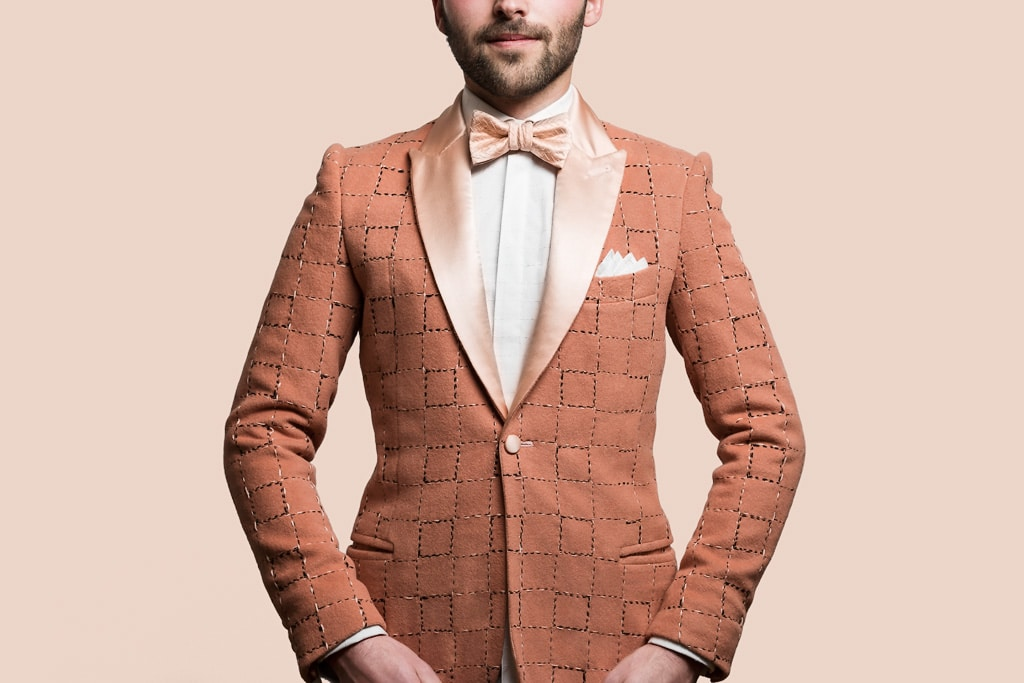 Blazer sur-mesure Monsieur List en laine rose saumon brodé main quadrillage coton rose et noir. Chemise et pochette de costume sur-mesure Monsieur List en coton brodé quadrillage coton blanc. Noeud papillon sur-mesure Monsieur List satin de soie rose saumon brodé chevrons soie rose. Fait en France. Photographie de Marcel Kultscher.