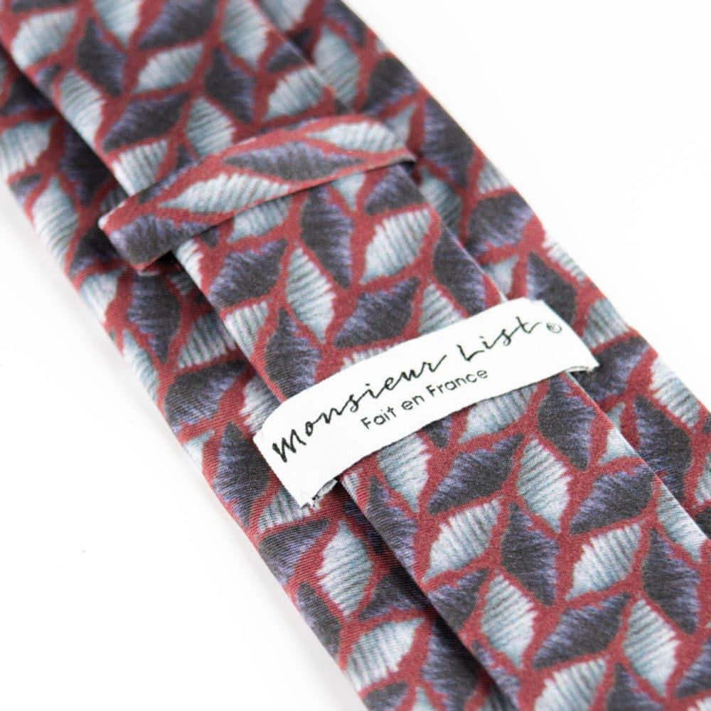 Cravate pièce unique Monsieur List soie bordeau imprimé club déconstruit losange brodé main bleu clair et gris. Fait en France. Photographie de Karl Arsène.