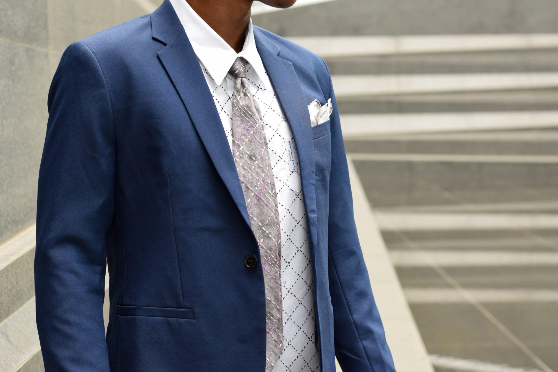 Cravate pièce unique Monsieur List soie grise imprimée quadrillage brodé à la main violet, rose et blanc. Fait en France. Photographie de Benjamin List.