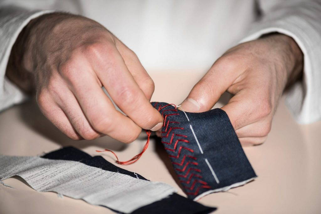 Nœud papillon sur-mesure Monsieur List laine bleu marine brodé chevrons à la main coton rouge. Fait en France. Photographie de Marcel Kultscher.